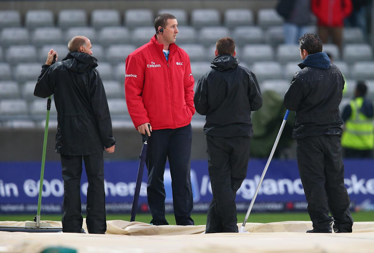 BIRMINGHAM, ENGLAND - SEPTEMBER 11:  Umpire Michael Gough inspects the pitch as rain stops play during the third NatWest One Day International Series match between England and Australia at Edgbaston on September 11, 2013 in Birmingham, England.  (Photo by Clive Mason/Getty Images)
