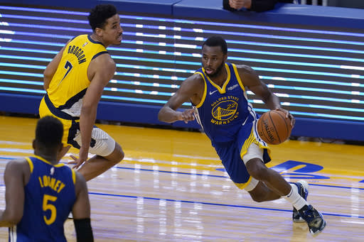 Golden State Warriors forward Andrew Wiggins (22) drives against Indiana Pacers guard Malcolm Brogdon (7) during the first half of an NBA basketball game in San Francisco, Tuesday, Jan. 12, 2021. (AP Photo/Jeff Chiu)