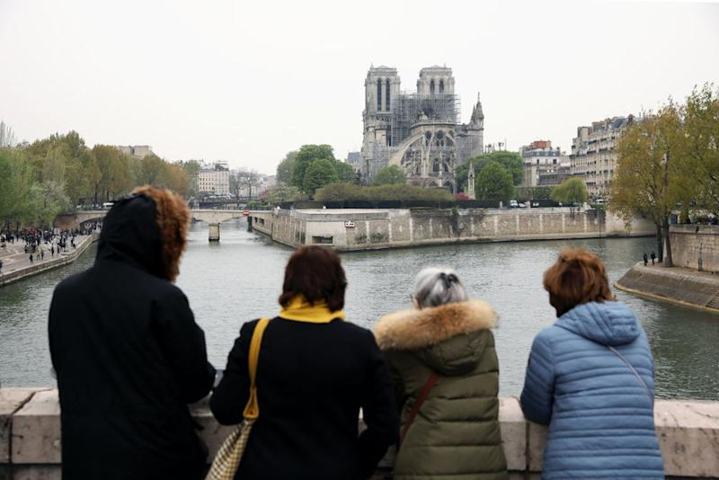 Onlookers gaze at the damage caused to Notre-Dame Cathedral following a major fire on April 16, 2019 in Paris, France. (Photo by Dan Kitwood/Getty Images)