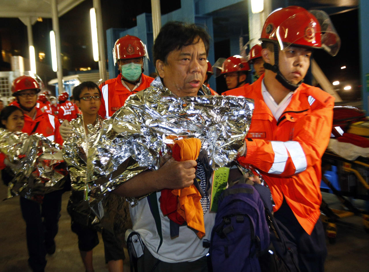 Survivors accompanied by rescuers, are taken onto shore after a collision involving two vessels in Hong Kong Tuesday, Oct. 2, 2012. Authorities in Hong Kong have rescued 101 people after a ferry collided with a boat and sank. A local broadcaster says eight people died.The government said in a statement that the ferry was carrying about 120 people when the accident happened Monday night near Lamma Island, off the southwestern coast of Hong Kong Island. Few other details were given. (AP Photo/Vincent Yu)