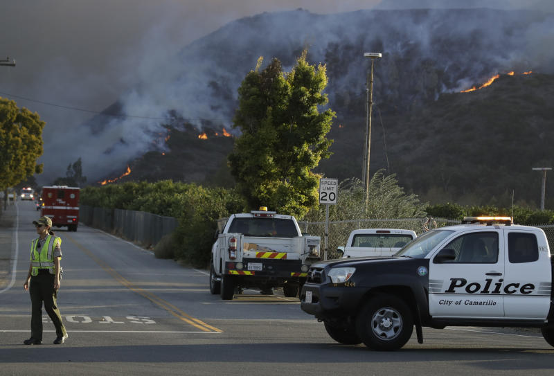 A police officer mans a checkpoint in front of an advancing wildfire Thursday, Nov. 8, 2018, near Newbury Park, Calif. The Ventura County Fire Department has ordered evacuation of some communities in the path of the fire, which erupted a few miles from the site of Wednesday night's deadly mass shooting at a Thousand Oaks bar. (AP Photo/Marcio Jose Sanchez)