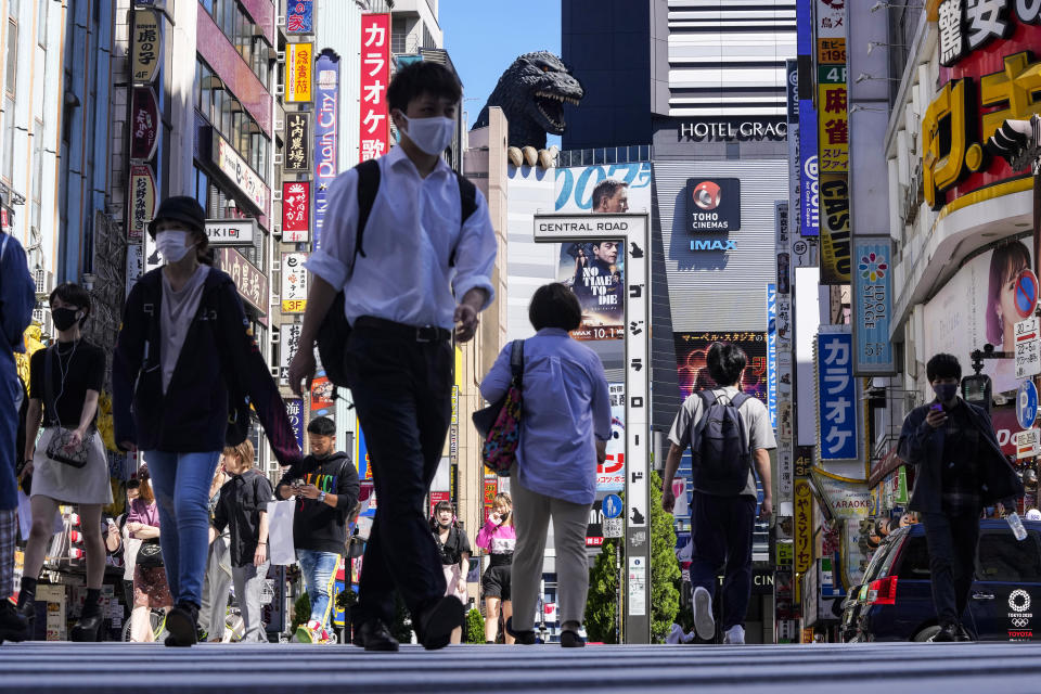 People wearing face masks to protect against COVID-19 walk past a crossing in Shinjuku, an entertainment district of Tokyo, Monday, Sept. 20, 2021. (AP Photo/Kiichiro Sato)