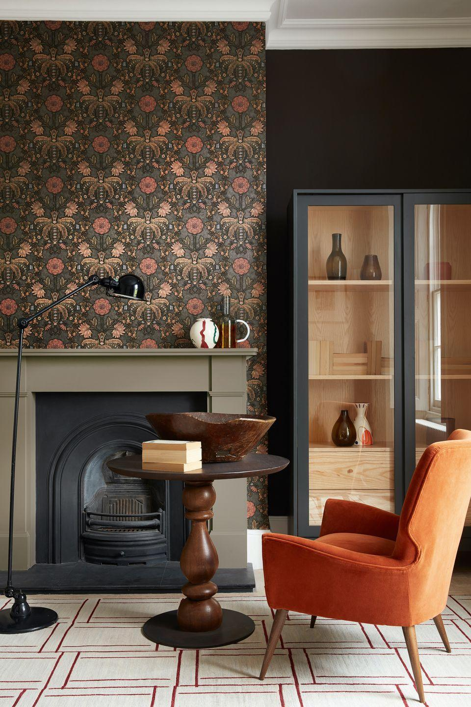"""<p>Don't be afraid to go dark in a living room – you can tie the scheme together with bold, punchy accents, like this burnt orange armchair. Wooden furniture grounds the scheme.<br></p><p>Pictured: London Wallpapers, New Bond Street - Hide, <a href=""""https://www.littlegreene.com/new-bond-street-hide"""" rel=""""nofollow noopener"""" target=""""_blank"""" data-ylk=""""slk:Little Greene"""" class=""""link rapid-noclick-resp"""">Little Greene</a></p>"""