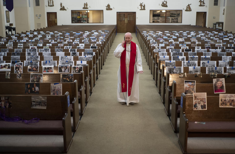 FILE - In this Friday, April 10, 2020 file photo, the Rev. Nicolas Sanchez takes a phone call from a parishioner after live-streaming the Good Friday Mass at St. Patrick's Catholic Church in Los Angeles. (AP Photo/Damian Dovarganes)