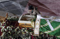 FILE - In this Saturday, Nov. 21, 2020 file photo, a woman mourns at the coffin of Patriarch Irinej as he lies in repose at the St. Sava Temple in Belgrade, Serbia. Patriarch Irinej died after testing positive for the coronavirus. He was 90. (AP Photo/Darko Vojinovic)