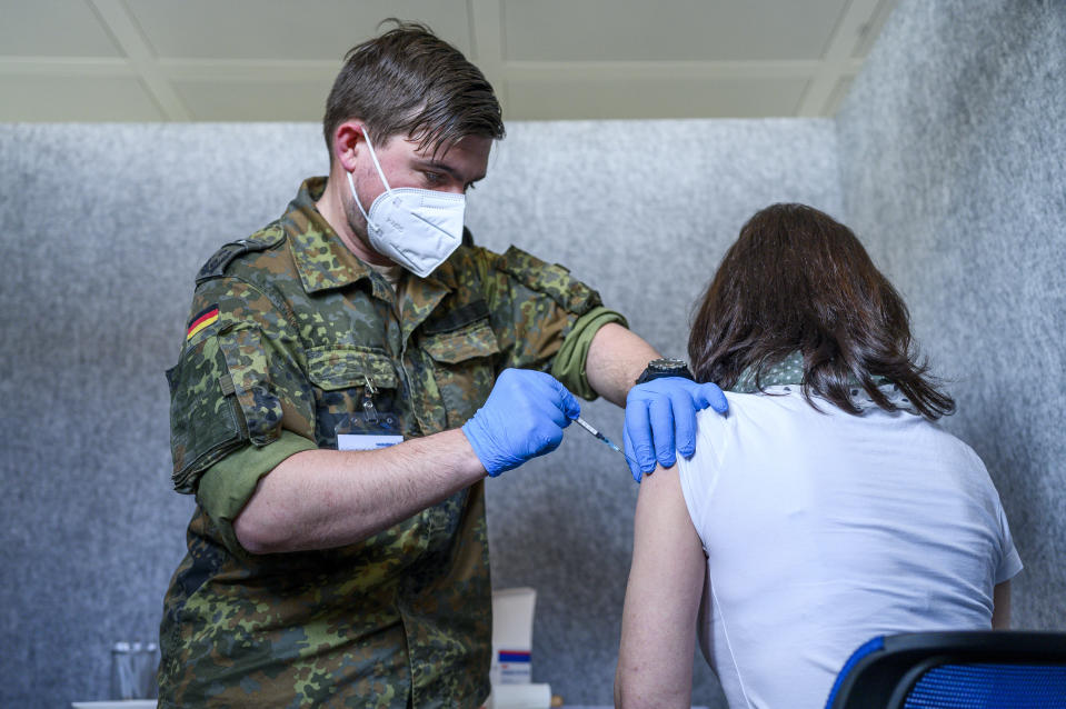 Michael Gebhardt from the German Armed Forces vaccinates an employee of Sander AG in Schwarzenbach an der Saale, Germany, Wednesday, April 28, 2021. Employees will be vaccinated against Covid-19 in vaccination booths built by Sander AG starting Wednesday.(Daniel Vogl/dpa via AP)