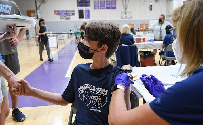 Shane Tebbens, age 12, holds his mother's hand while a nurse gives him a shot of the Pfizer COVID-19 vaccine at a vaccination clinic at Winter Springs High School. (Paul Hennessy/SOPA Images/LightRocket via Getty Images)