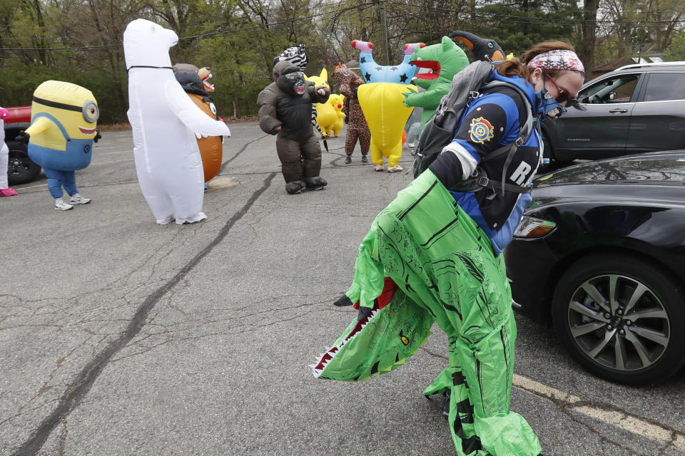 In this Monday, May 11, 2020 photo, Keely Crimando, a member of the T-Rex Walking Club, puts on her costume in Ferndale, Mich. The group takes its unannounced strolls through neighborhoods on a quest to bring smiles to the faces of kids, and a few adults, while under Michigan's stay-at-home order because of the COVID-19 pandemic. (AP Photo/Carlos Osorio)
