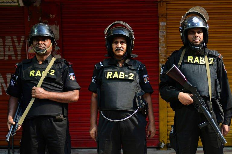Bangladeshi Rapid Action Battalion (RAB) personnel stand guard during a nationwide strike in Dhaka on March 4, 2013