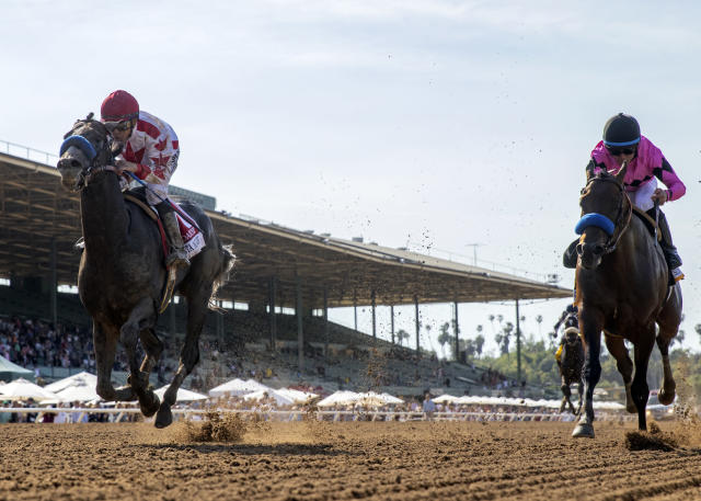 In this image provided by Benoit Photo, Roadster, left, with Mike Smith aboard, overpowers Game Winner, right, with Joel Rosario aboard, to win the Grade I, $1,000,000 Santa Anita Derby horse race Saturday, April 6, 2019, at Santa Anita Park in Arcadia, Calif. (Benoit Photo via AP)