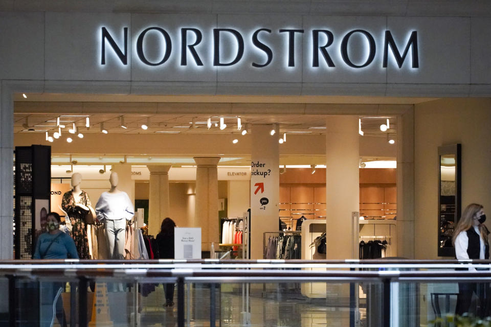 Shoppers walk near an entrance to a Nordstrom store at a shopping mall in Pittsburgh on Wednesday, Feb. 24, 2021.  Nordstrom says it's acquiring a minority interest in four fashion brands owned by a British company called Asos as the department store aims to reach out to younger customers. The brand - Topshop, Topman, Miss Selfridge and HIIT - were purchased by Asos in February after their previous owner and British fashion empire Arcadia Group filed for bankruptcy in late 2020.  (AP Photo/Keith Srakocic)