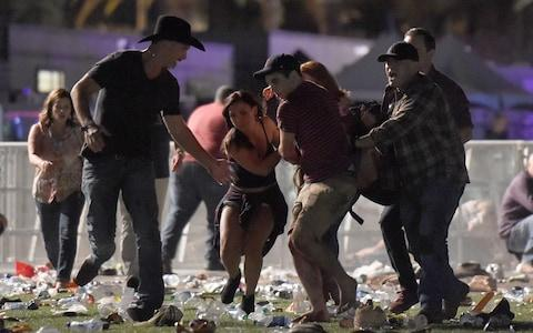 People carry a person at the Route 91 Harvest country music festival after apparent gunfire - Credit: David Becker/Getty Images