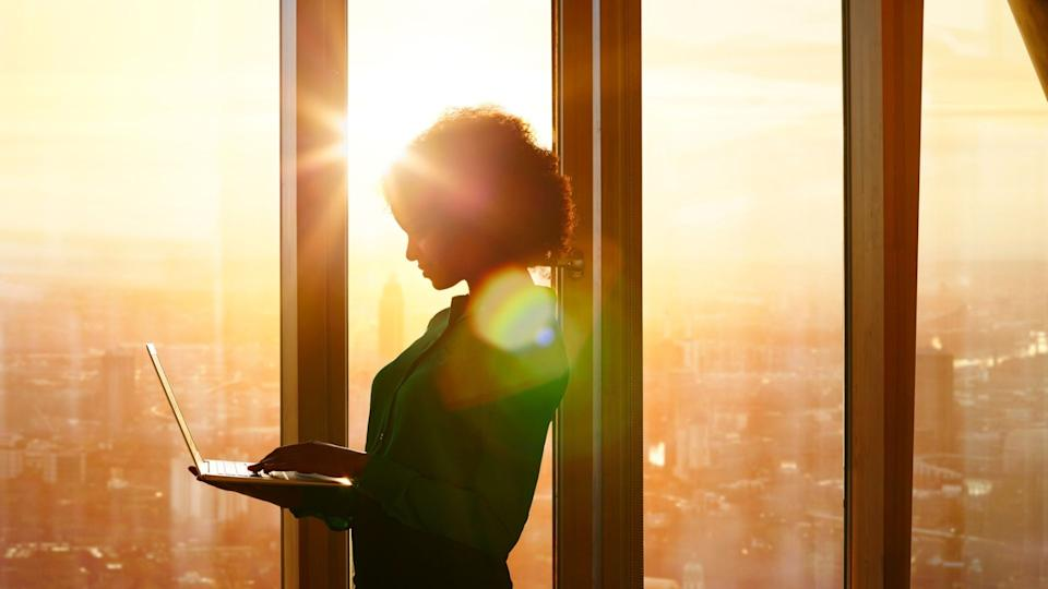 Woman standing up using laptop by high rise window with sunset in the background.