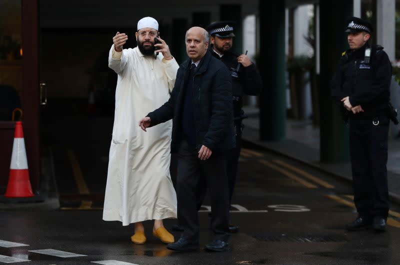 A man gestures as Police officers are seen outside the London Central Mosque in London