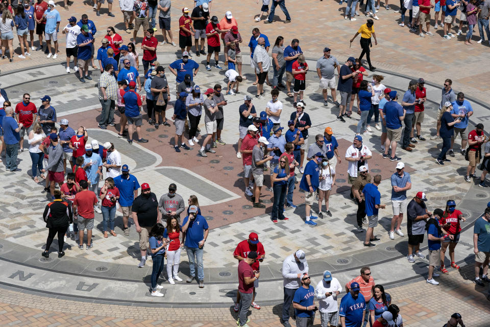 Fans line up to enter Globe Life Field before the Texas Rangers home opener baseball game against the Toronto Blue Jays Monday, April 5, 2021, in Arlington, Texas. The Texas Rangers are set to have the closest thing to a full stadium in pro sports since the coronavirus shutdown more than a year ago. (AP Photo/Jeffrey McWhorter)