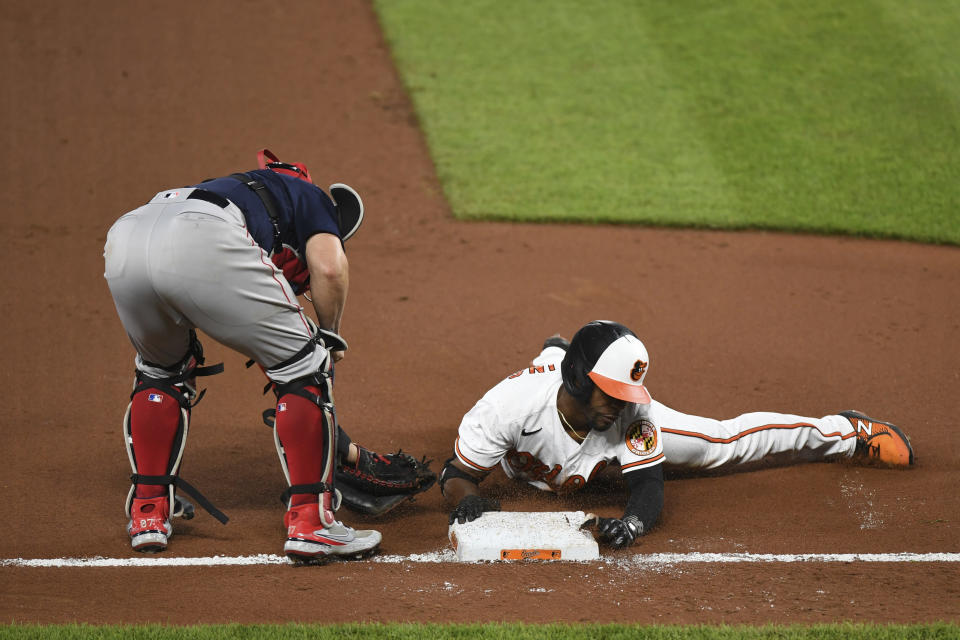 Baltimore Orioles Cedric Mullins slides into third and avoids tag from Boston Red Sox catcher Christian Vazquez for eighth inning triple during a baseball game Monday, May 10, 2021, in Baltimore. (AP Photo/Terrance Williams)