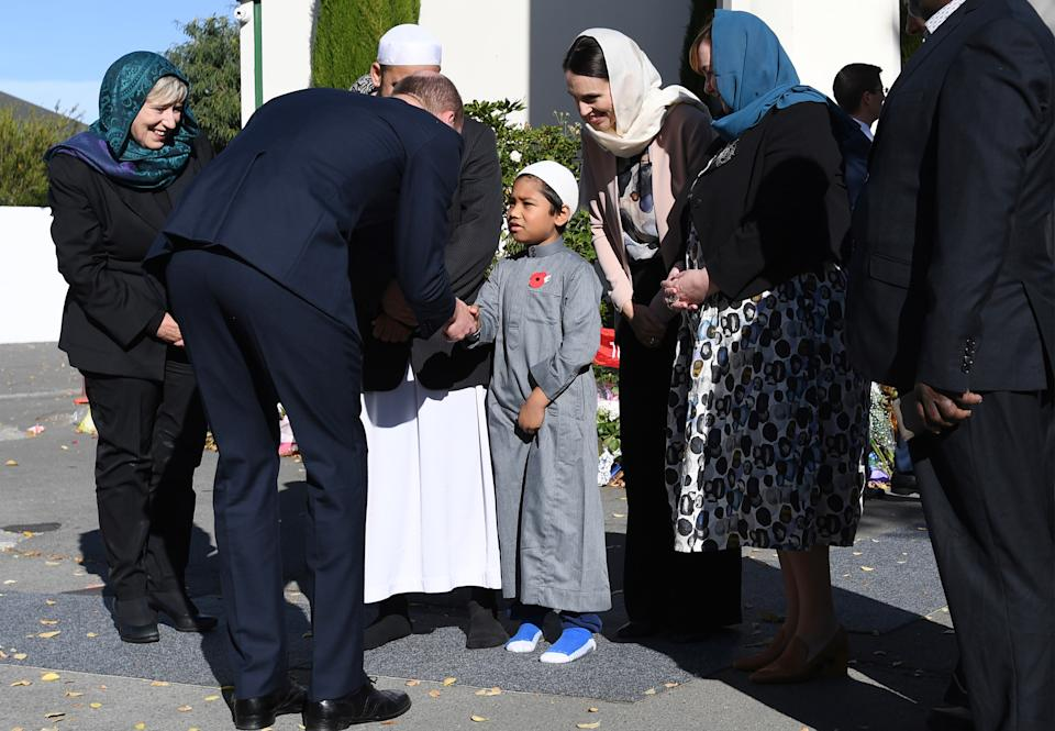 Britain's Prince William (L) greets a boy as New Zealand Prime Minister Jacinda Ardern (C) looks on at the Al Noor mosque in Christchurch on April 26, 2019. - Prince William is on a two day visit to New Zealand to show his support for Christchurch after the resent mosque attacks that claimed 50 lives. (Photo by TRACEY NEARMY / POOL / AFP)        (Photo credit should read TRACEY NEARMY/AFP via Getty Images)