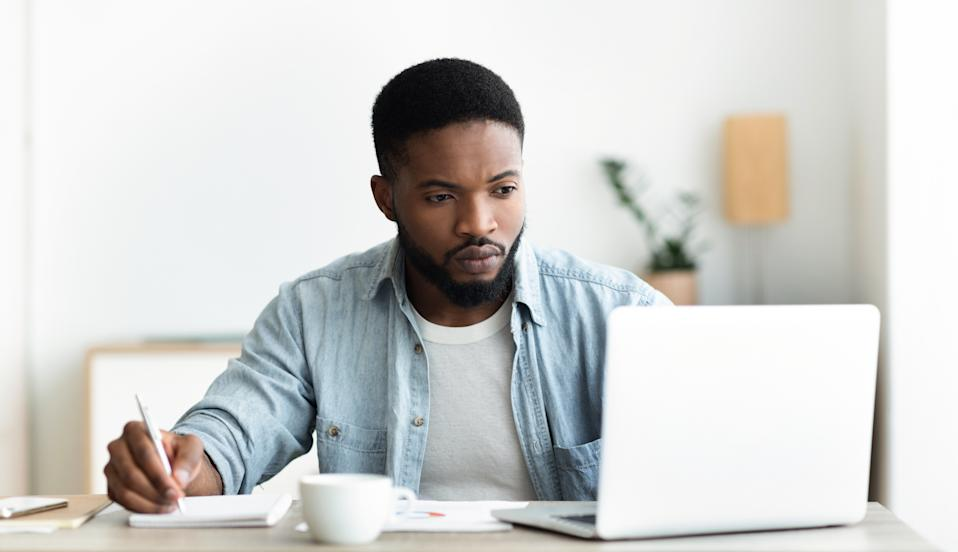 Job search. Unemployed man using laptop searching for vacancies online in internet and taking notes, panorama with copy space