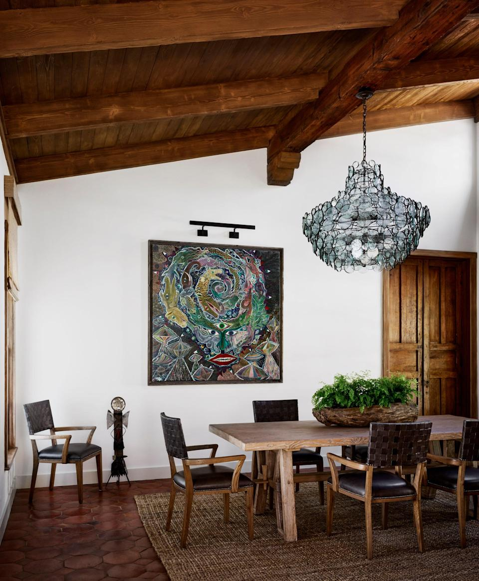 A Currey & Company chandelier of glass disks recycled from the bottoms of wine and soda bottles makes a sculptural statement in the dining room. The painting is by Haitian artist Frantz Zephirin.