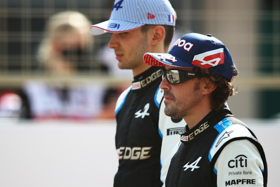 BAHRAIN, BAHRAIN - MARCH 12: Esteban Ocon of France and Alpine F1 Team and Fernando Alonso of Spain and Alpine F1 Team stand on the grid during Day One of F1 Testing at Bahrain International Circuit on March 12, 2021 in Bahrain, Bahrain. (Photo by Joe Portlock/Getty Images)