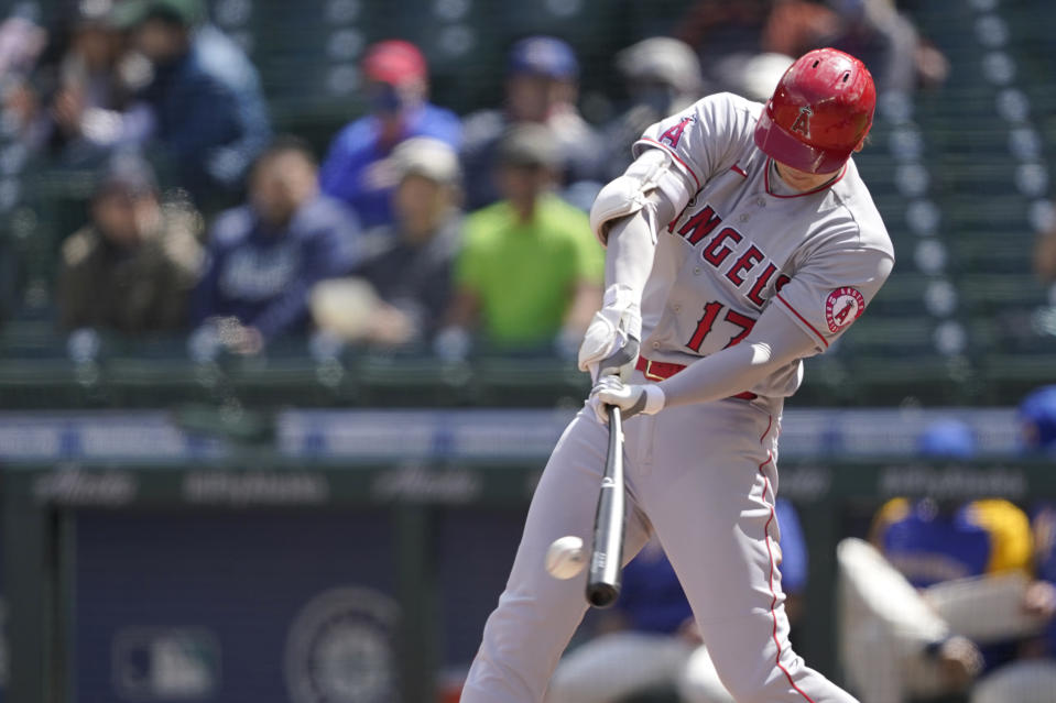 Los Angeles Angels Shohei Ohtani hits into a play where he reached first base on a fielding error during the third inning of a baseball game, Sunday, May 2, 2021, in Seattle. (AP Photo/Ted S. Warren)