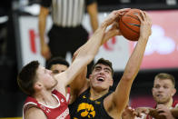 Iowa center Luka Garza fights for a rebound with Wisconsin forward Micah Potter, left, during the first half of an NCAA college basketball game, Sunday, March 7, 2021, in Iowa City, Iowa. (AP Photo/Charlie Neibergall)