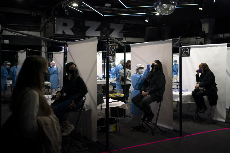 Health workers are tested for coronavirus ahead of a music concert in Barcelona, Spain, Saturday, March 27, 2021. Five thousand music lovers are set to attend a rock concert in Barcelona on Saturday after passing a same-day COVID-19 screening to test its effectiveness in preventing outbreaks of the virus at large cultural events. The show by Spanish rock group Love of Lesbian has the special permission of Spanish health authorities. While the rest of the country is limited to gatherings of no more than four people in closed spaces, the concertgoers will be able to mix freely while wearing face masks. (AP Photo/Emilio Morenatti)