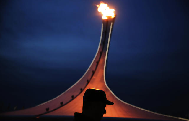 A visitor to Olympic Park is silhouetted while walking past the Olympic cauldron at the 2014 Winter Olympics, Thursday, Feb. 20, 2014, in Sochi, Russia. (AP Photo/David Goldman)