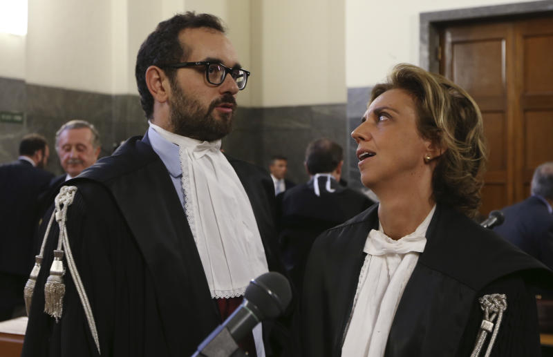 Prosecutors Laura Pedio and Gaetano Ruta look at each others prior to the sentence at the Milan's court Italy, Wednesday, June 19, 2013. A Milan court convicted fashion designers Domenico Dolce and Stefano Gabbana of tax evasion. The pair were found guilty Wednesday of failing to declare euros 1 billion ($1.3 billion) in income to authorities. The court sentenced them both to one year and eight months in jail. Prosecutors argued that the pair had evaded taxes on income of 416 million euros each and 200 million euros through a Luxembourg-based company. The statute of limitations ran out on a charge of misrepresenting income. (AP Photo/Luca Bruno)