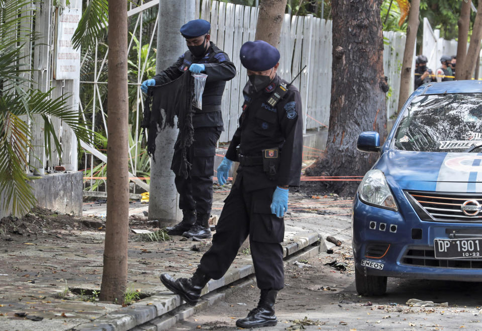 A member of the police bomb squad, left, holds a piece of clothes found at the site of Sunday's suicide bomb attack at the Sacred Heart of Jesus Cathedral in Makassar, South Sulawesi, Indonesia, Monday, March 29, 2021. Two attackers believed to be members of a militant network that pledged allegiance to the Islamic State group blew themselves up outside the packed Roman Catholic cathedral during a Palm Sunday Mass on Indonesia's Sulawesi island, wounding a number of people, police said. (AP Photo/Yusuf Wahil)