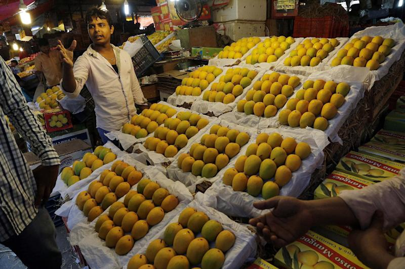 In this Tuesday, May 6, 2014 photo, an Indian vendor talks to a customer as Alphonso mangoes are displayed at a whole sale market in Mumbai, India. Starting May 1, the EU banned imports of Indian mangoes including the Alphonso, considered the king of all the mango varieties available in South Asia. The ban was implemented because a large number of shipments were contaminated with fruit flies. (AP Photo/Rajanish Kakade)