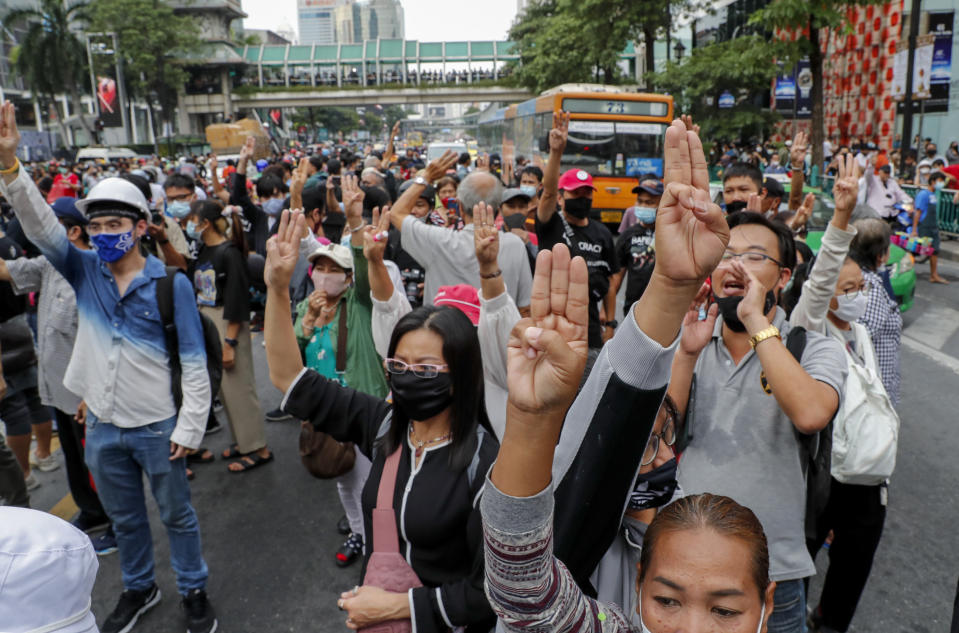 Pro-democracy protesters flash three-fingers salute during a protest rally at Ratchaprasong business district in Bangkok, Thailand, Sunday, Oct. 25, 2020.. Pro-democracy protesters in Thailand gathered again Sunday in Bangkok, seeking to keep up pressure on the government a day ahead of a special session of Parliament called to try to ease political tensions. (AP Photo/Gemunu Amarasinghe)