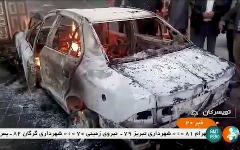 People stand near a burning car in Zanjan, Iran, in this still image taken from video on January 1, 2018 - Credit: REUTERS