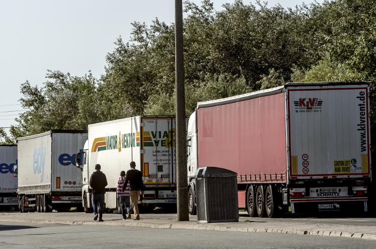 Migrants walk past UK-bound lorries in Calais, northern France, on August 5, 2014