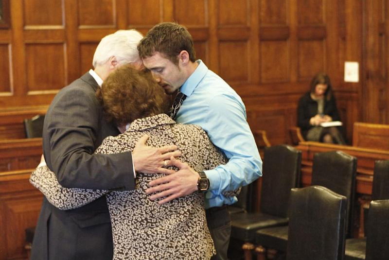 Mark Strong Sr., his wife Julie and their son Bradley hug during a recess in Cumberland County Unified Criminal Court in Portland, Maine, on Thursday, March 21, 2013. Julie Strong was overcome with emotion while addressing Justice Nancy Mills so Mills called for a recess to allow Strong to compose herself. Mark Strong was sentenced to 20 days in jail and ordered to pay $3,000 in fines. In the background at right is Sarah Churchill, attorney for Alexis Wright.  (AP Photo/Portland Press Herald, Gregory Rec, Pool)