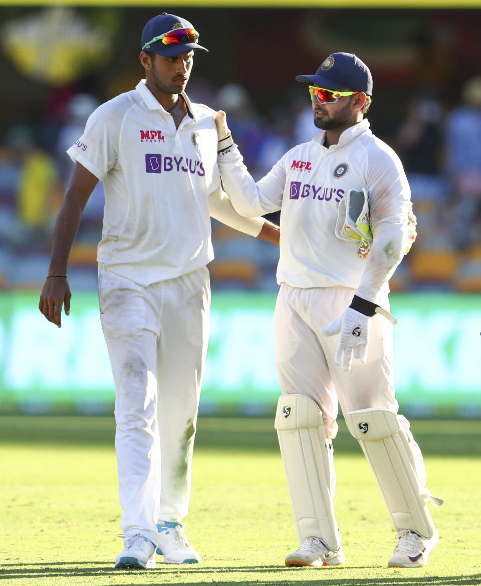 India's Washington Sundar, left, is congratulated by teammate Rishabh Pant following play on the first day of the fourth cricket test between India and Australia at the Gabba, Brisbane, Australia, Friday, Jan. 15, 2021. (AP Photo/Tertius Pickard)