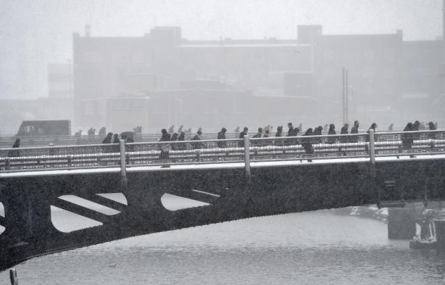 CHICAGO, IL - MARCH 5: Pedestrians cross the Chicago River on March 5, 2013 in Chicago, Illinois. The worst winter storm of the season is expected to dump 7-10 inches of snow on the Chicago area with the worst expected for the evening commute. (Photo by Brian Kersey/Getty Images)