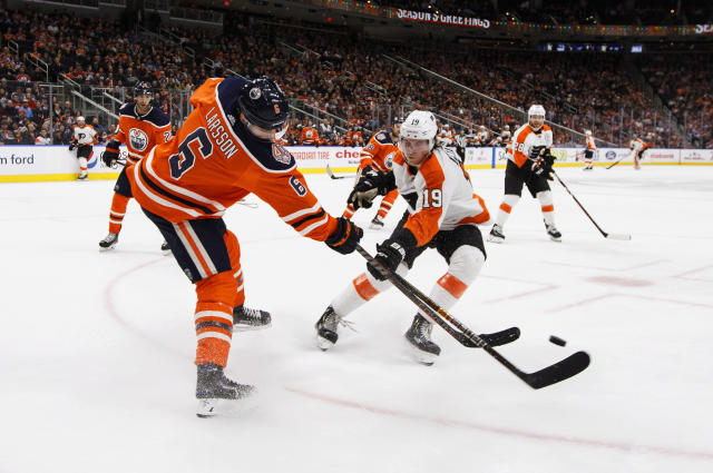 Philadelphia Flyers' Nolan Patrick (19) and Edmonton Oilers' Adam Larsson (6) battle for the puck during the third period of an NHL hockey game in Edmonton, Alberta, on Friday, Dec. 14, 2018. (Jason Franson/The Canadian Press via AP)