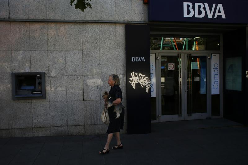 A woman and her dog walk out of a BBVA bank branch in Madrid