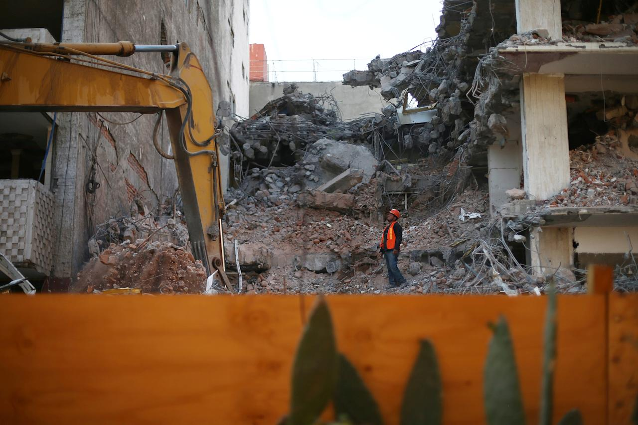 An employee works at a site where a building is demolished, five months after the September 19 earthquake, in the Los Alamos neighborhood in Mexico City, Mexico February 15, 2018. Picture taken February 15, 2018. REUTERS/Edgard Garrido
