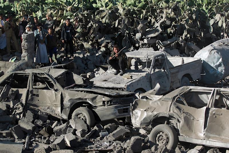 Yemenis stand next to burnt vehicles following Saudi air strikes against Huthi rebels near Sanaa Airport on March 26, 2015 (AFP Photo/Mohammed Huwais)