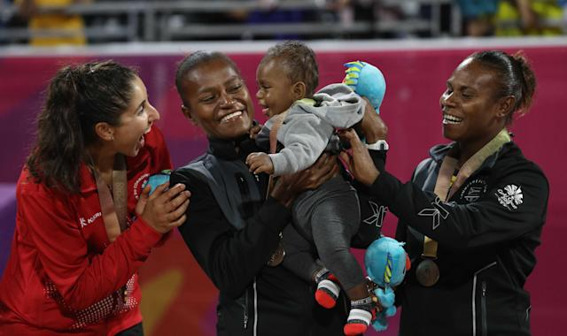 Beach Volleyball - Gold Coast 2018 Commonwealth Games - Women's Medal Ceremony - Coolangatta Beachfront - Gold Coast, Australia - April 12, 2018. Bronze medalists Miller Pata and Linline Matauatu of Vanuatu stand on a podium with a child. REUTERS/Athit Perawongmetha
