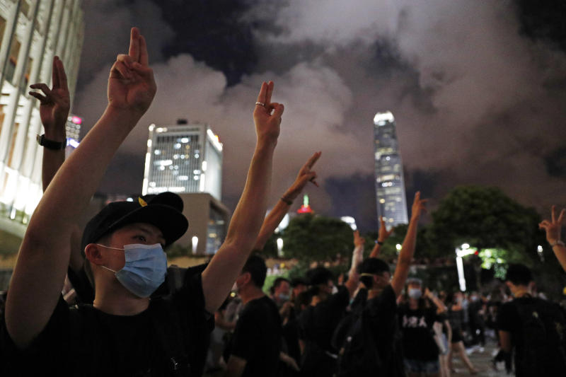 "In this Monday, July 1, 2019 photo, protesters use hand signals to gestures for scissors during their attempt to break into the Legislative building in Hong Kong. Protesters use hand signals to communicate which supplies need to be delivered to the front lines. Arms circling the head indicate ""helmets,"" while a forward cutting motion made by the index and middle fingers signals ""scissors."" The items are then passed through a human chain. (AP Photo/Vincent Yu)"