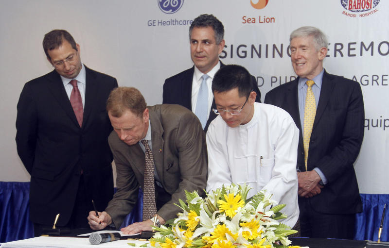 President and CEO of General Electric ASEAN, Stuart Dean, second from left, signs documents during the signing ceremony between Sea Lion Co. Ltd., General Electric Healthcare and Bahosi and Pun Hlaing Hospitals in Yangon, Myanmar, Saturday, July. 14, 2012. General Electric became the first American firm to sign a business deal in Myanmar after Washington eased key investment sanctions on the former pariah state. Witness at the signing are from left., U.S. ambassador to Myanmar Derek Mitchell, Stuart Dean, U.S. Under Secretary of Commerce for International Trade, Francisco Sanchez, Managing Director of SEA Lion, Win Zaw Aung and U.S. Under Secretary of State for Economic Growth, Energy and the Environment, Robert Hormats. (AP Photo/Khin Maung Win)