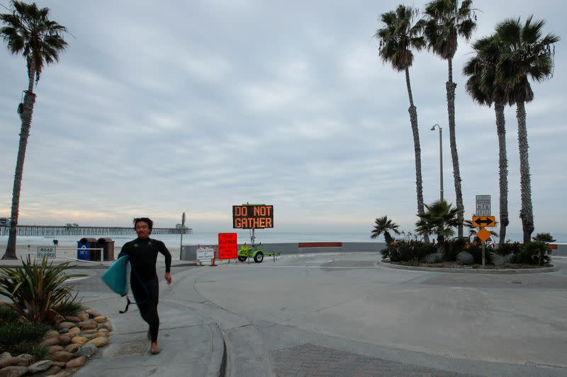 A surfer passes a warning sign on the beach as new stay-at-home orders begin in Southern California