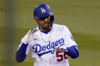 Los Angeles Dodgers' Mookie Betts gestures toward his bench after hitting a ground rule double during the first inning of a baseball game against the Cincinnati Reds Monday, April 26, 2021, in Los Angeles. (AP Photo/Mark J. Terrill)