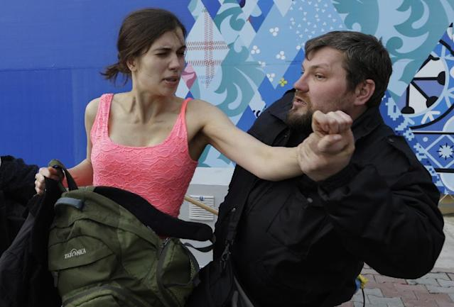 A russian security officer attacks Nadezhda Tolokonnikova and a photographer as she and fellow members of the punk group Pussy Riot, including Maria Alekhina, left, stage a protest performance in Sochi, Russia, on Wednesday, Feb. 19, 2014. The group had gathered in a downtown Sochi restaurant, about 30km (21miles) from where the Winter Olympics are being held. They ran out of the restaurant wearing brightly colored clothes and ski masks and were set upon by about a dozen Cossacks, who are used by police authorities in Russia to patrol the streets. (AP Photo/Morry Gash)