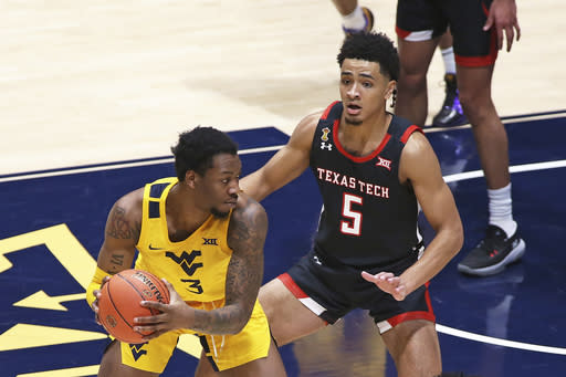 West Virginia forward Gabe Osabuohien (3) is defended by Texas Tech guard Micah Peavy (5) during the second half of an NCAA college basketball game Monday, Jan. 25, 2021, in Morgantown, W.Va. (AP Photo/Kathleen Batten)