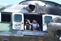 Brazilian President Jair Bolsonaro waves from a helicopter as he flies over the Brasilia rally on May 15, 2021