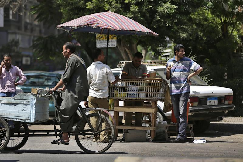 Egyptians eat at an open-air cart restaurant, in Cairo, Egypt, Sunday, Sept. 8, 2013. An Egyptian military official says helicopter gunships have launched new strikes targeting militant hideouts in the northern Sinai peninsula, on a second day of a major offensive aiming at quelling an insurgency in the lawless region. (AP Photo/Hassan Ammar)